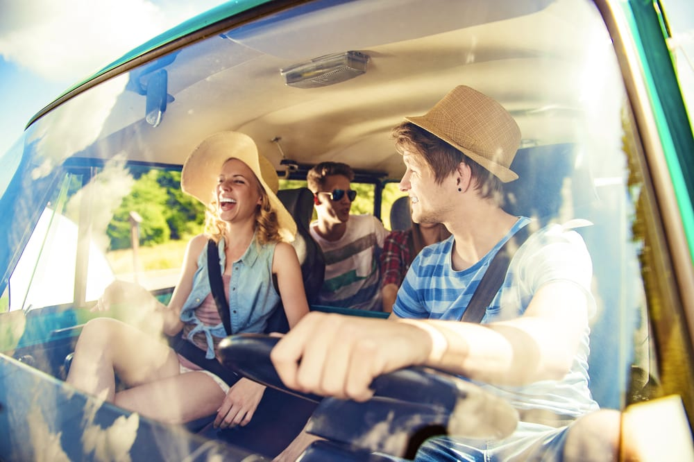 group of young adults driving to a music festival
