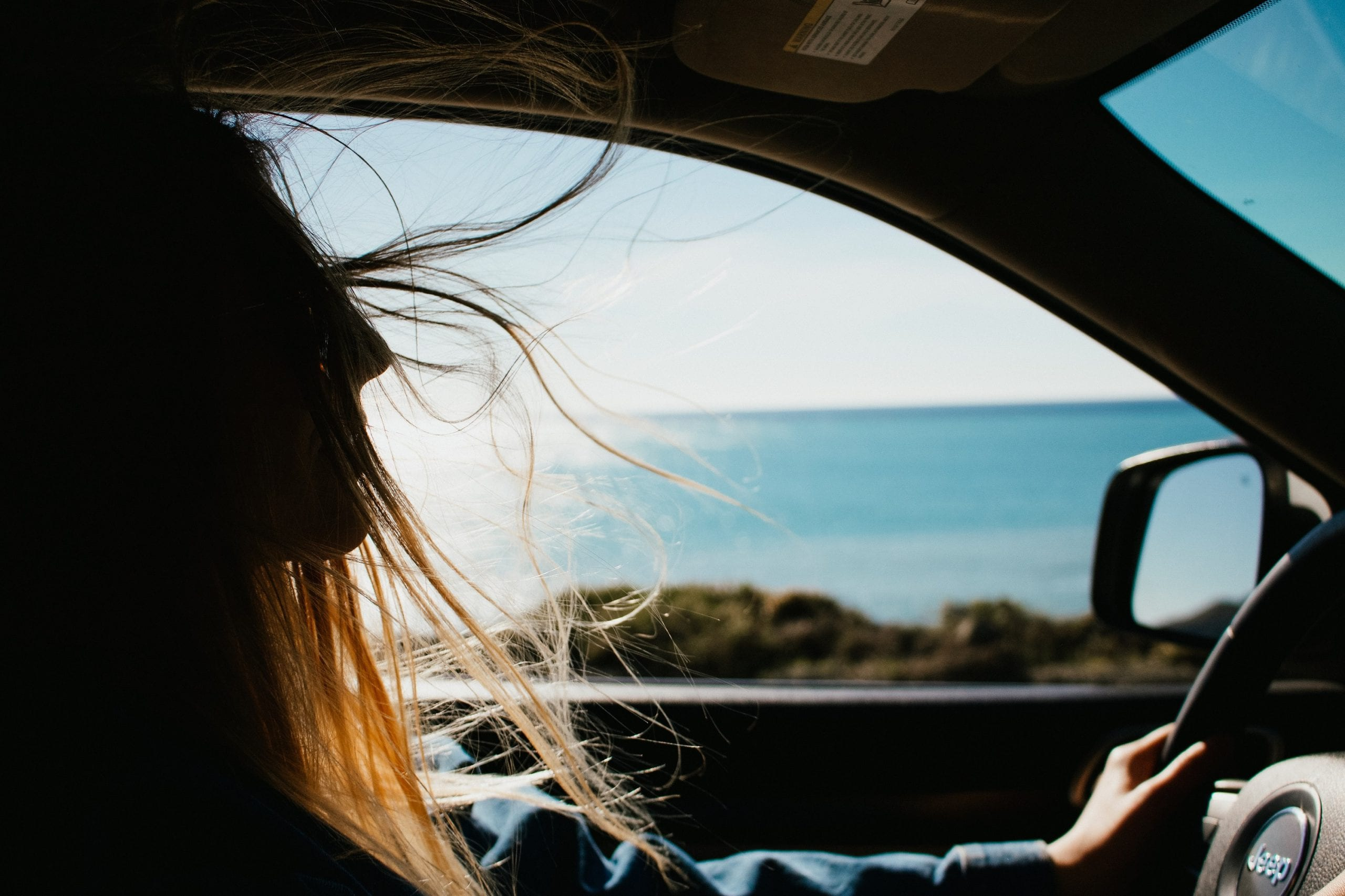 A girl driving by the sea in the car