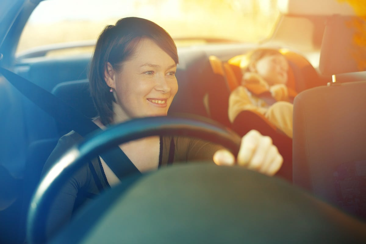 Woman driving with small child in the back