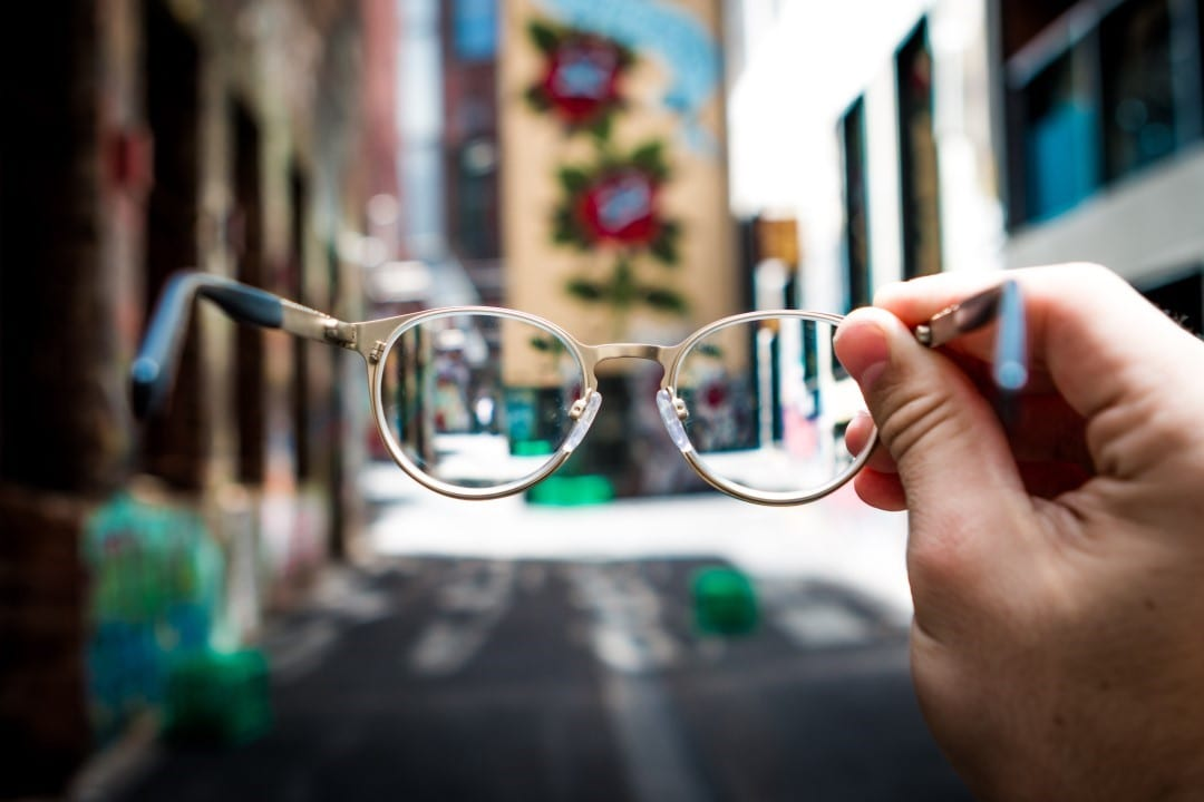 A person holding up their glasses