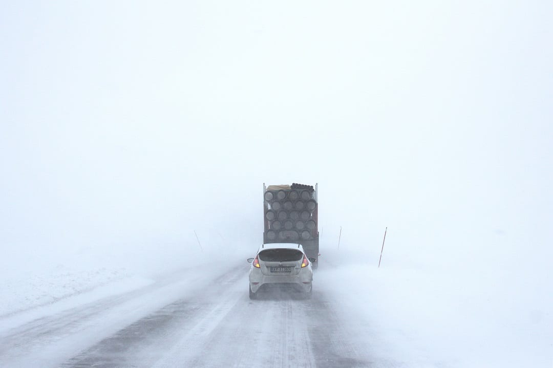 Snow on the road with a car and a lorry