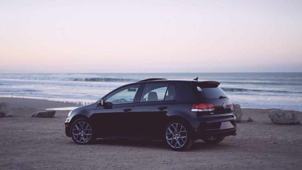 a black car by the sea