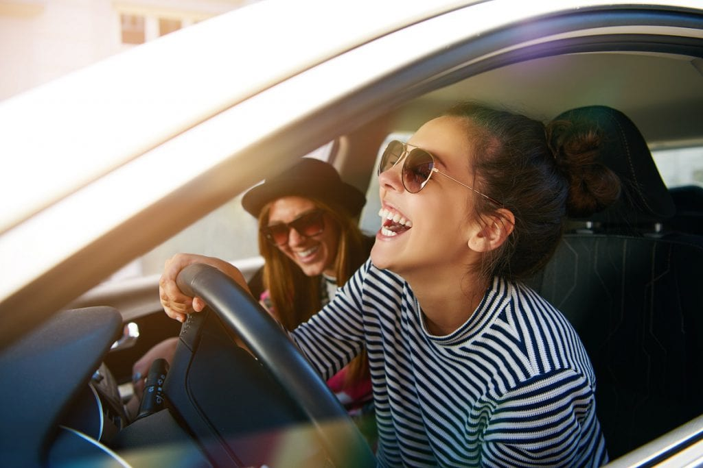 woman driving in car with friends