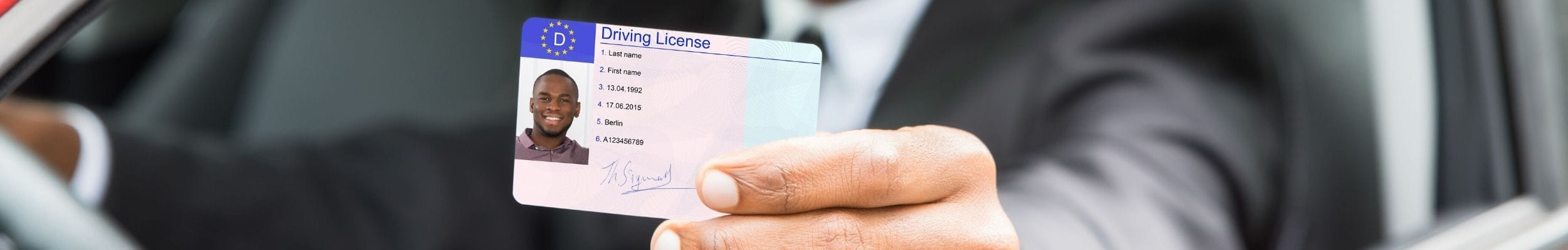 Young man holding driving licence in car